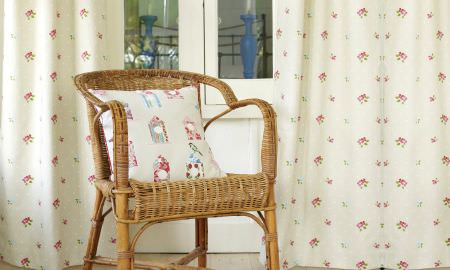 Prestigious Textiles -  Butterfly Gardens Fabric Collection - Wicker corner chair with cream cushion and curtains showing colourful Butterfly Gardens fabric designs