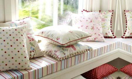 Prestigious Textiles -  Butterfly Gardens Fabric Collection - Summery window seat with colourful stripe pattern and a variety of spotted, striped and floral throw cushions