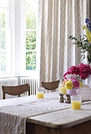 Prestigious Textiles -  Canvas Fabric Collection - Solid rustic wood table and chairs with a pale table runner, long cream and grey patterned curtains, glasses and vases