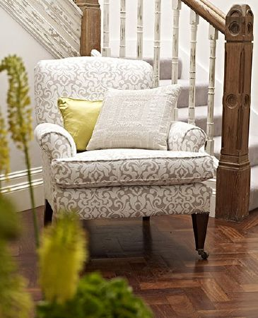 Prestigious Textiles -  Canvas Fabric Collection - A staircase with an armchair padded with a light brown and white patterned fabric, with a lime green and white cushions
