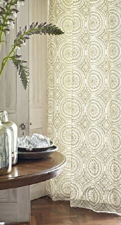 Prestigious Textiles -  Canvas Fabric Collection - Translucent floor-length curtains featuring a cream and grey circular print, with a round wood table and silver vases