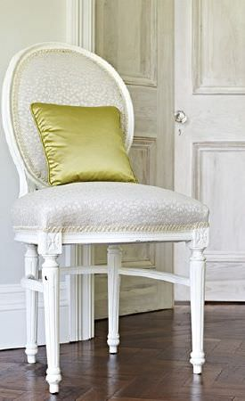 Prestigious Textiles -  Canvas Fabric Collection - White chair with a wood frame and a padded grey and white seat and back, with a plain apple green coloured cushion