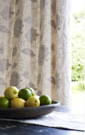 Prestigious Textiles -  Canvas Fabric Collection - Thin pale grey and cream floral patterned curtains with a solid black table with a white runner, a wooden bowl and fruit