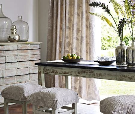 Prestigious Textiles -  Canvas Fabric Collection - A distressed wood dresser with a black and white rustic wood table, and wood stools with padded grey and white fabric seats