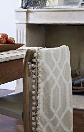 Prestigious Textiles -  Canvas Fabric Collection - Beige and white patterned, pompom-edged throw draped over a solid rustic wood chair beside a wooden table with a bowl