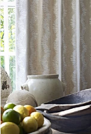 Prestigious Textiles -  Canvas Fabric Collection - Various pottery and wood bowls and urns holding fruit and utensils in front of light beige and white patterned curtains
