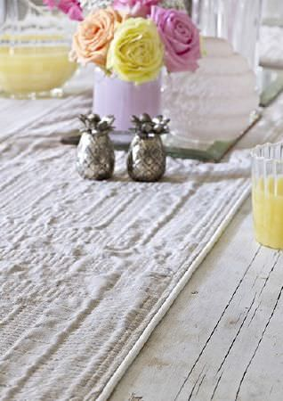 Prestigious Textiles -  Canvas Fabric Collection - A textured white table runner on a pale wood table with silver pineapple shaped salt and pepper pots, a glass and a jug