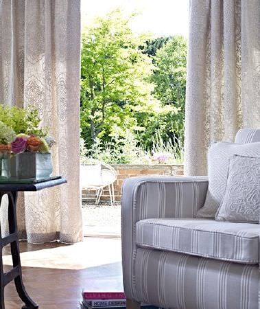 Prestigious Textiles -  Canvas Fabric Collection - Light grey and white striped armchair with two pale cushions, long cream and beige patterned cushions and a black table