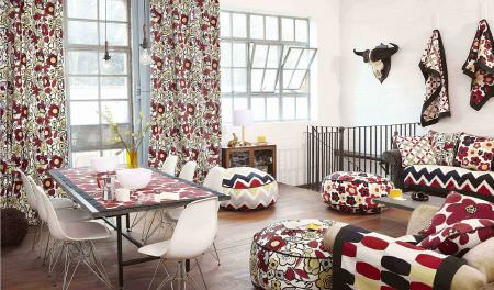 Prestigious Textiles -  Carnaby Fabric Collection - Red, black and cream patterned sofa, armchair, cushions, footstools, curtains, blankets, dining table, with plain white plastic chairs