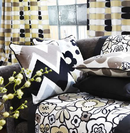 Prestigious Textiles -  Carnaby Fabric Collection - Dark grey sofa, with brown, white and black zigzag cushion, and flower print cushions and a throw, with multicoloured curtains