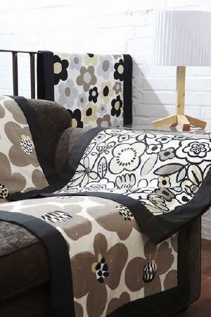 Prestigious Textiles -  Carnaby Fabric Collection - Cream, brown, black and gold stylised floral print blankets with wide black borders, a dark grey sofa and a wooden lamp with white lampshade