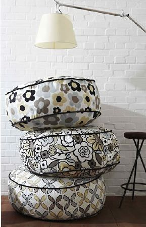 Prestigious Textiles -  Carnaby Fabric Collection - Round fabric footstools in grey, white, gold and black patterns, with a cream shaded anglepoise lamp and a folding black stool