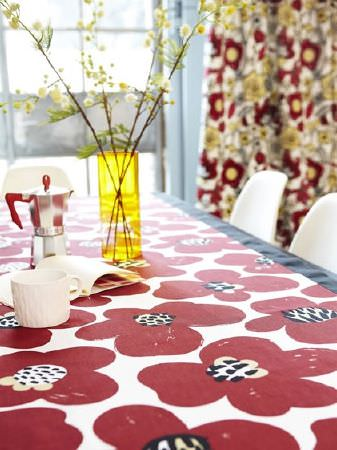 Prestigious Textiles -  Carnaby Fabric Collection - Poppy print tablecloth with black trim, white chairs, red and yellow patterned curtains, a yellow translucent vase, cafetiere and white mug