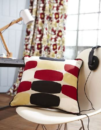 Prestigious Textiles -  Carnaby Fabric Collection - Cream plastic chair with red, black, cream and yellow cushion, headphones, bright patterned curtains and a wood and white angled desk lamp