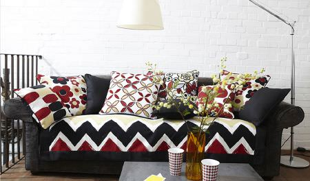 Prestigious Textiles -  Carnaby Fabric Collection - Black, red, white and yellow sofa with matching scatter cushions, a large shaded anglepoise lamp, table, yellow vase and red and white mugs
