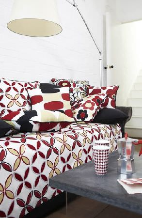 Prestigious Textiles -  Carnaby Fabric Collection - Sofa with red, black, white and cream pattern, coordinating cushions, a low grey table, cafetiere, red and white mugs and a large floor lamp