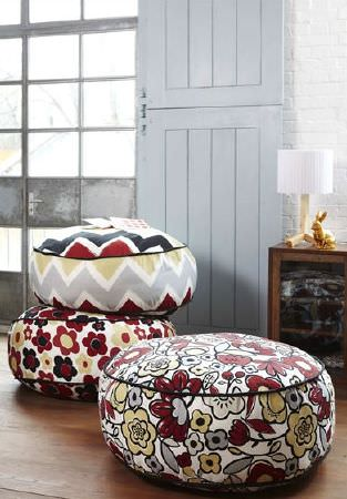 Prestigious Textiles -  Carnaby Fabric Collection - Soft round beanbag type patterned footstools, with a glass fronted display case and a small wooden lamp with a white shade