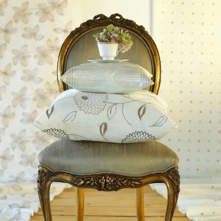 Prestigious Textiles -  Carnival Fabric Collection - Antique grey/gold upholstered chair with white pillows with classic floral and stripe decoration for a great classic feeling