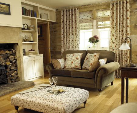 Prestigious Textiles -  Charm Fabric Collection - A rustic country house with white curtains with red flower print, a padded coffee table with classic vine design and an upholstered couch