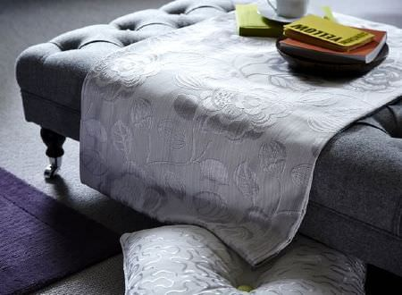 Prestigious Textiles -  Clifton Fabric Collection - Large, low, grey fabric-covered seat, with silver floral fabric, a silver patterned cushion, a purple rug and a black plate