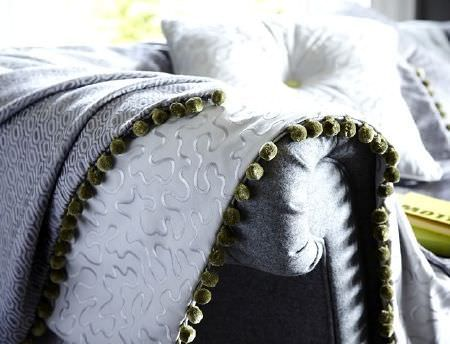 Prestigious Textiles -  Clifton Fabric Collection - White fabric with silver embroidery and grey patterned fabric, both fringed, on a grey sofa with a white cushion