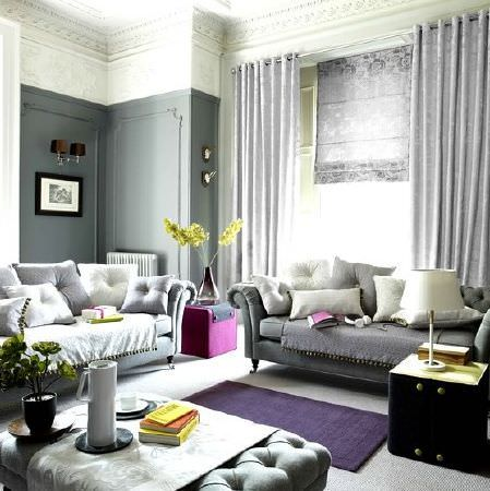 Prestigious Textiles -  Clifton Fabric Collection - Two sofas in different shades of grey, with a grey footstool, scatter cushions, grey curtains, purple rug, black chest and a cream lamp