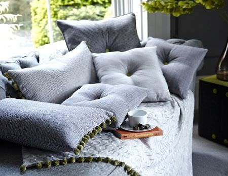 Prestigious Textiles -  Clifton Fabric Collection - Grey sofa with plain, patterned and checked grey fabric cushions, some fringed with green pompoms, fringed white embroidered fabric