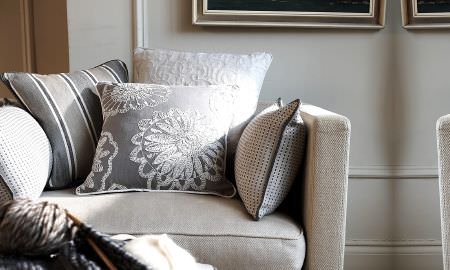 Prestigious Textiles -  Clover Fabric Collection - Comfy oatmeal armchair with cream and grey cushions, modern embroidered floral and striped patterns