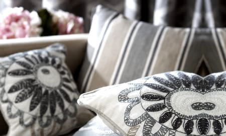 Prestigious Textiles -  Clover Fabric Collection - Cream and grey cushions with modern embroidered design and grey, tan and cream striped cushion.