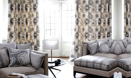 Prestigious Textiles -  Clover Fabric Collection - Modern lounge area in muted tones of grey, tan and cream, showing striped and embroidered cushions and matching curtains