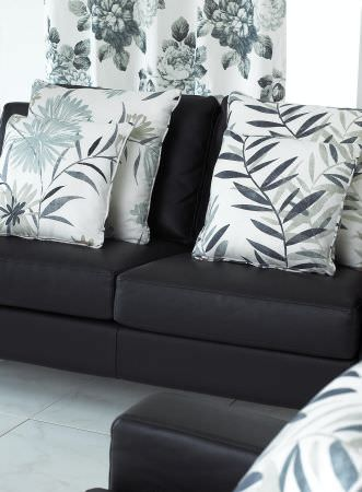 Prestigious Textiles -  Cocktail Fabric Collection - White cushions with modern simple foliage pattern on a black upholstered couch, and a classic white curtain with detailed floral decorations
