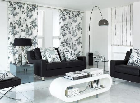 Prestigious Textiles -  Cocktail Fabric Collection - Modern living room setting with black upholstered couches and white pillows with modern leaf patterns, and a white curtain with flowers