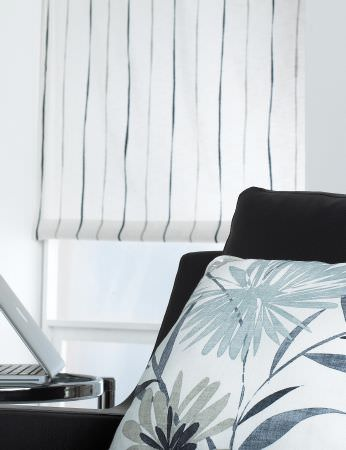 Prestigious Textiles -  Cocktail Fabric Collection - Modern striped white roman blind, a white cushion decorated with a modern foliage pattern and a black upholstered couch