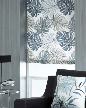 Prestigious Textiles -  Cocktail Fabric Collection - White roman blind decorated with large blue palm leaves, and a pillow with a modern leaf design