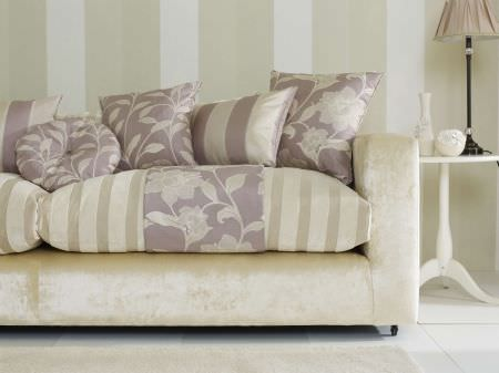 Prestigious Textiles -  Cordoba Fabric Collection - Faded purple square and round cushions with a classic simple leaf pattern on an oyster white couch upholstery with stripes