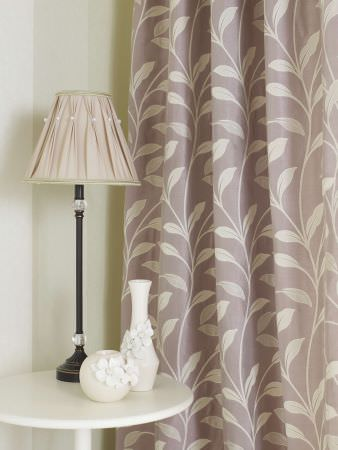 Prestigious Textiles -  Cordoba Fabric Collection - A faded purple curtain with white simple vertical vines and leaves, and a classic pinched lamp shade