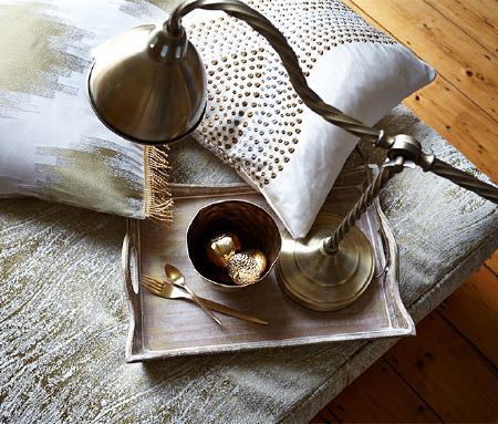 Prestigious Textiles -  Cosmopolitan Fabric Collection - A silver lamp, bowl and cutlery on a distressed wood tray, with luxurious gold, silver and white scatter and seat cushions