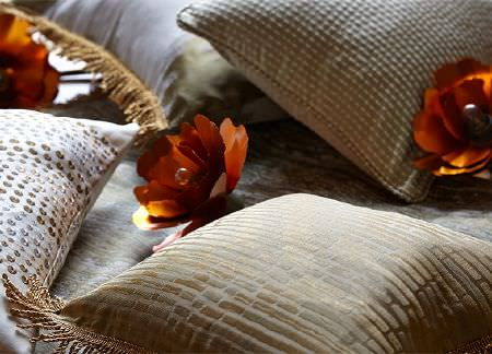 Prestigious Textiles -  Cosmopolitan Fabric Collection - Rust coloured metallic foil roses scattered with gold, silver and white dotted and striped cushions with gold fringing