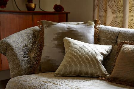 Prestigious Textiles -  Cosmopolitan Fabric Collection - Subtle textures and bold patterns covering silver, gold and cream cushions with fringing, on a subtly patterned silver sofa