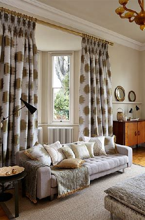 Prestigious Textiles -  Cosmopolitan Fabric Collection - A pale purple sofa with dark gold and whtie-grey patterned curtains, pale scatter cushions and a silver footstool and throw