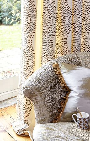 Prestigious Textiles -  Cosmopolitan Fabric Collection - Gold and silver dotted wavy lines on white curtains, with a silver-white sofa, and a gold and white cushion with fringing