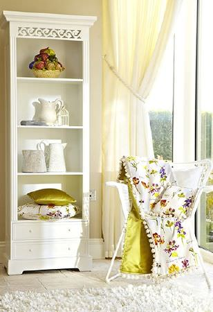 Prestigious Textiles -  Country Fair Fabric Collection - Tall, narrow, white wood unit with shelves and drawers, with a white wicker chair, green and floral fabric and cushions, and cream curtains
