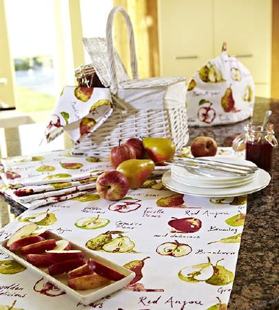 Prestigious Textiles -  Country Fair Fabric Collection - Table runner, napkins and teapot cover, all in white, green and red apple and pear print fabric, with white picnic basket and white crockery