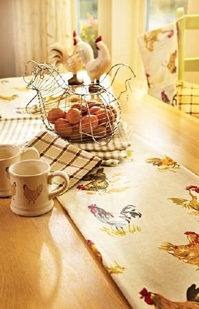 Prestigious Textiles -  Country Fair Fabric Collection - Wood table, chicken print fabric and napkins, brown and white checked napkins, with a wire chicken shaped egg holder and chicken print mugs