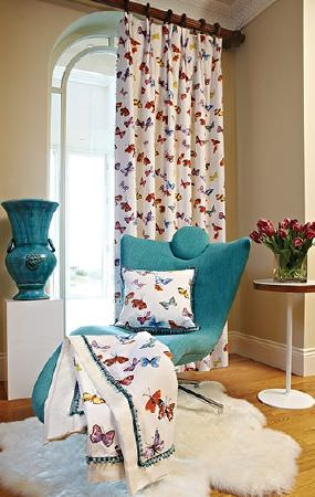 Prestigious Textiles -  Country Fair Fabric Collection - Turquoise reclining chair, coloured butterfly print blanket, curtains and cushion, white sheepskin rug, round white table and turquoise urn