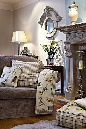 Prestigious Textiles -  Country Fair Fabric Collection - Mocha coloured sofa, brown and white checked, striped and duck print cushions and fabric, round grey framed mirror, lamp, urn, candle holder