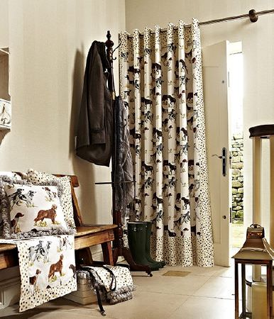 Prestigious Textiles -  Country Fair Fabric Collection - Dog print fabric framed with dotted fabric, made into curtains, blankets and cushions, with a wooden bench, black coat hanger, and lantern