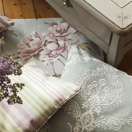 Prestigious Textiles -  Country House Fabric Collection - Pastel coloured cushions with stripes, flowers, and an embroidered lace design, with a rustic set of drawers