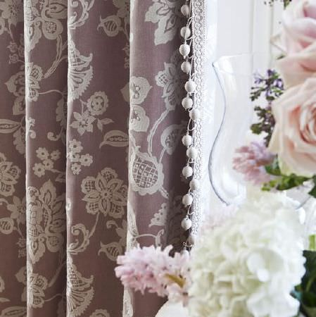 Prestigious Textiles -  Country House Fabric Collection - Pink-brown fabric with cream embroidered lace effect and bobble tassels, with a glass vase