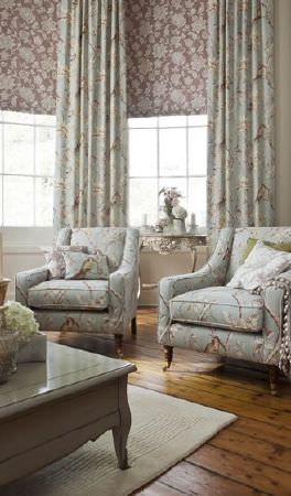Prestigious Textiles -  Country House Fabric Collection - Pale blue armchairs and curtains with bird and floral patterns, scatter cushions, ornate wooden side and coffee tables, and patterned blinds